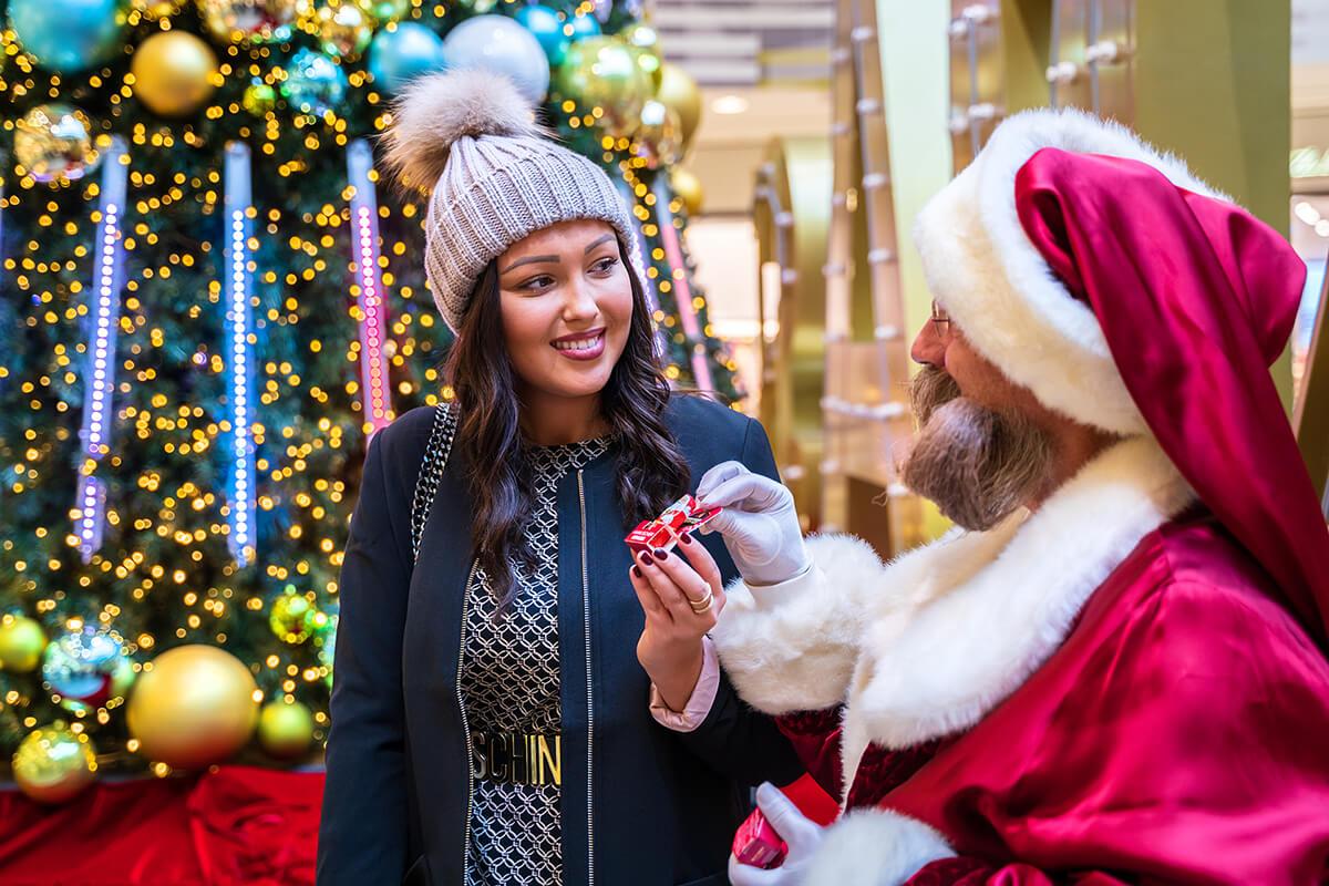 Junge Frau bekommt ein Geschenk vom Weihnachtsmann